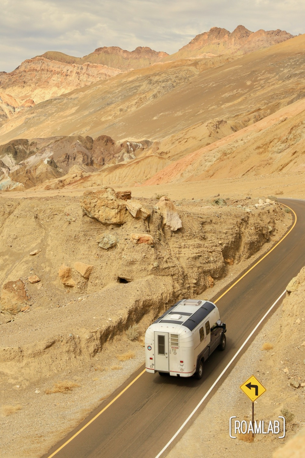 1970 Avion C11 truck camper driving through Artist's Road in Death Valley National Park.