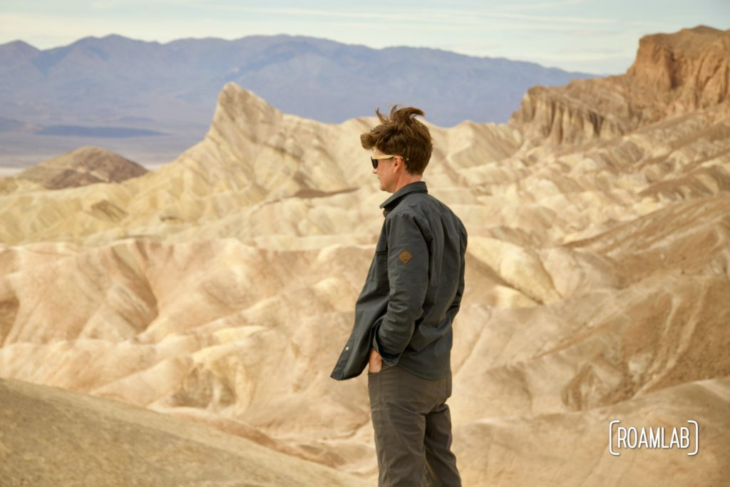 Man standing in front of a rock formation at Zabrinskie Point, Death Valley National Park, California