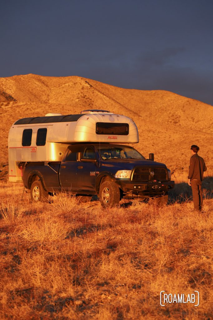 The golden rays of the sunrise casting the landscape and a 1970 Avion C11 truck camper and man in gold.