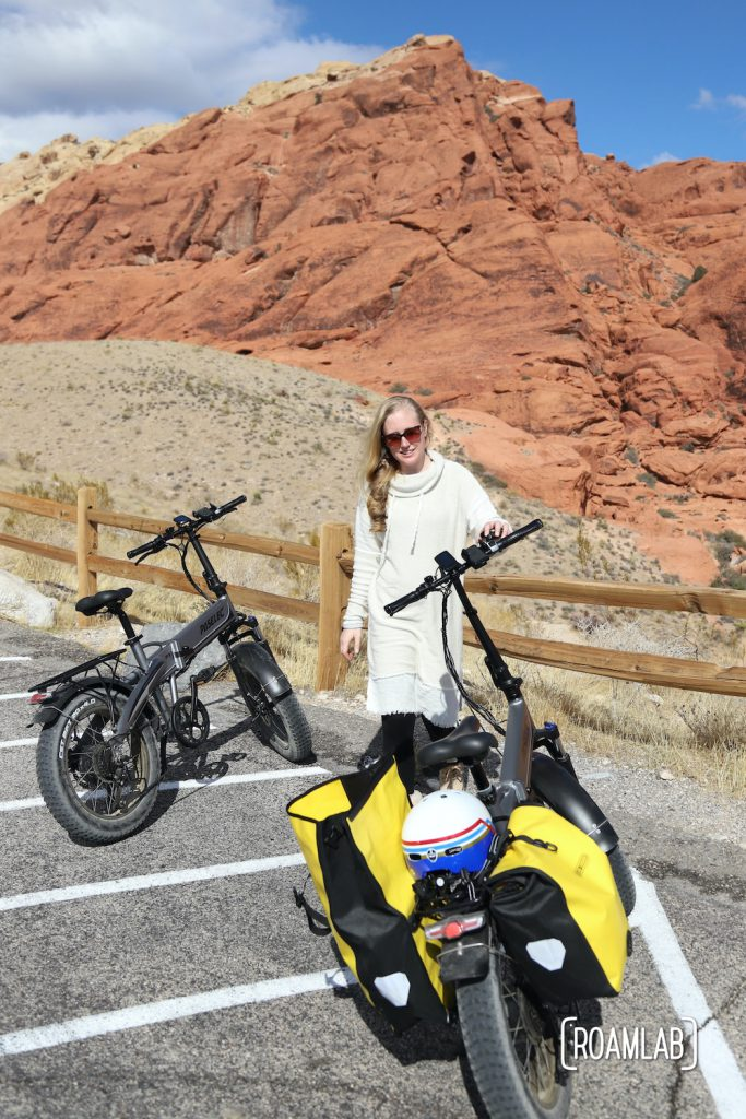 Woman standing next to her bike with a red cliff behind her.