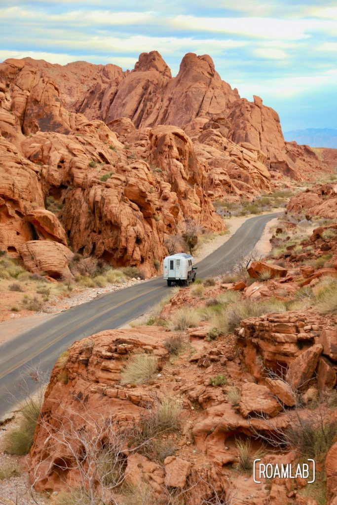 1970 Avion C11 truck camper flanked by red rocks driving down Mouse Tank Road in Valley of Fire State Park.