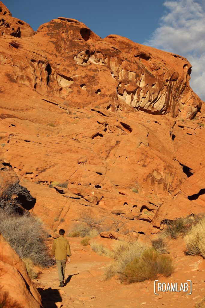 Man dwarfed by the red cliffs of Mouse Tank Trail in Valley of Fire State Park.