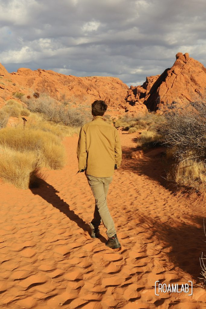 Man walking through the red sand on Mouse Tank Trail of Valley of Fire State Park