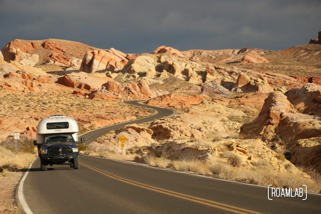 1970 Avion C11 truck camper driving through a rainbow of red rocks down Mouse Tank Road in Valley of Fire State Park.
