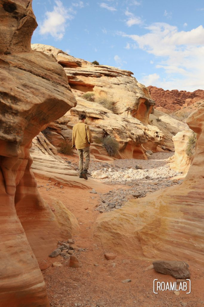 Man wandering through a red sandstone wash in White Domes Trail in Nevada's Valley of Fire State Park.