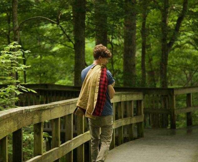 Man strolling down the shady boardwalk of the Heritage Trail Loop in Kentucky's Mammoth Cave National Park.