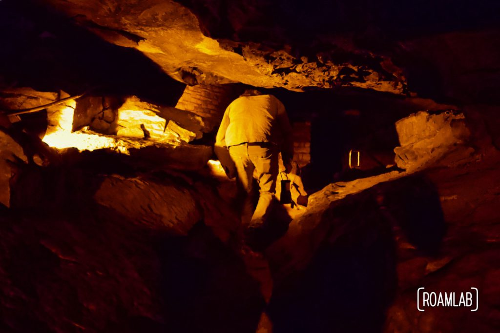 Man crawling through Tall Man's Misery on the Geology Tour of Mammoth Cave National Park.