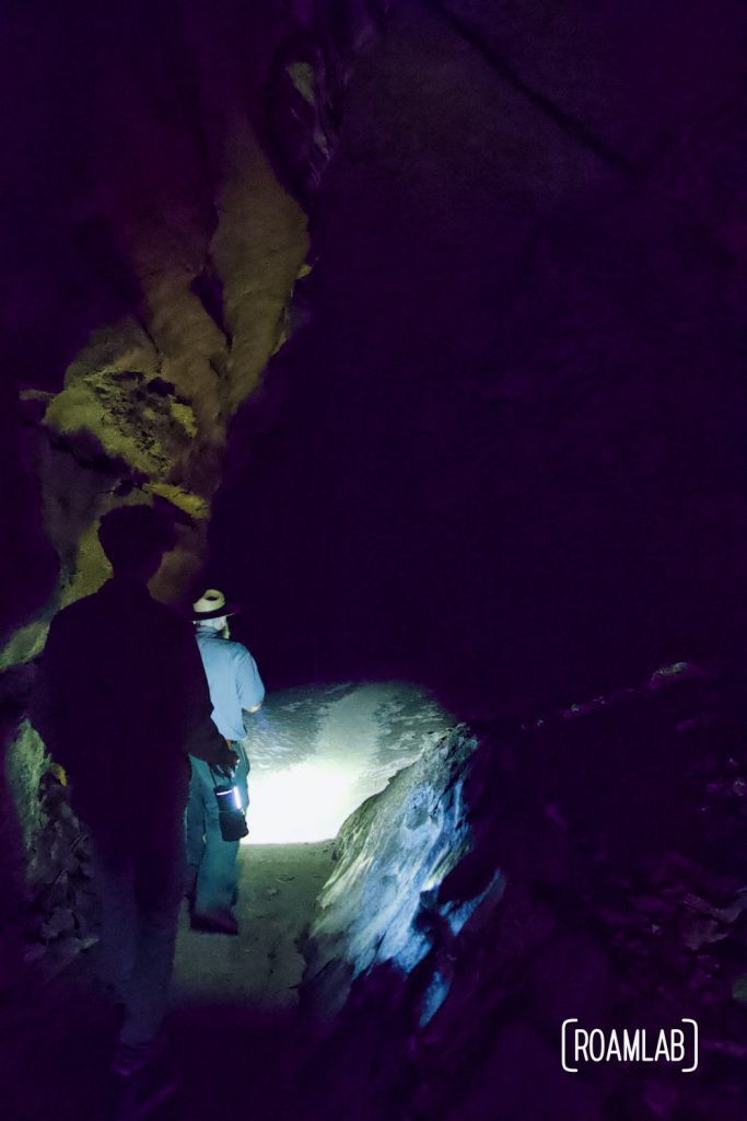 Man walking through a dark cave, faintly lit by lantern on the Geology Tour of Mammoth Cave National Park.