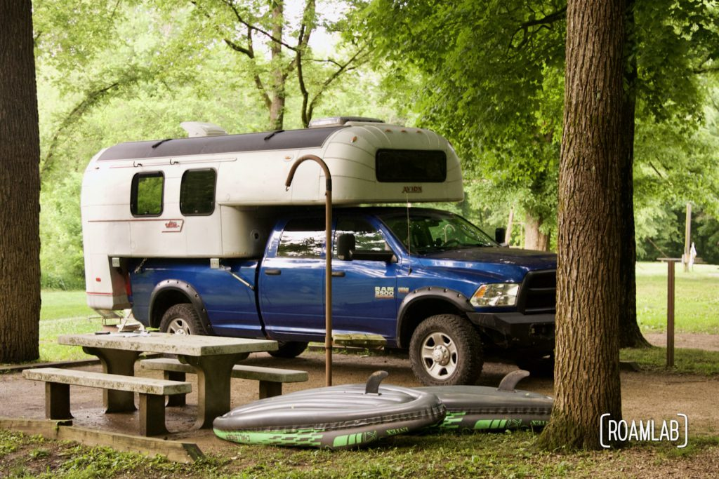 1970 Avion C11 truck camper in parked at the Houchin Ferry Campground in Mammoth Caves National Park with a picnic table and kayaks in the foreground.