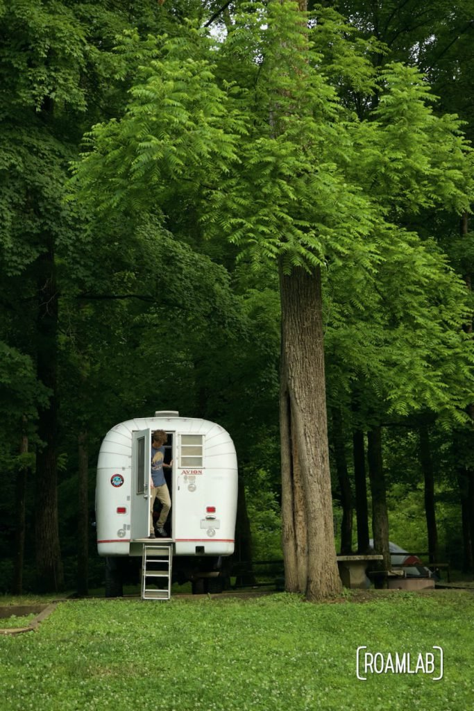 Man stepping out of a 1970 Avion C11 truck camper at Houchin Ferry Campground in Mammoth Cave National Park.