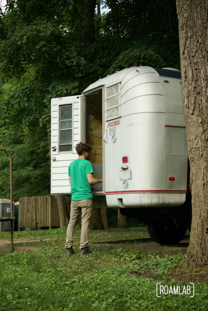 Man standing at door of a 1970 Avion C11 truck camper at the Houchin Ferry Campground in Mammoth Cave National Park.