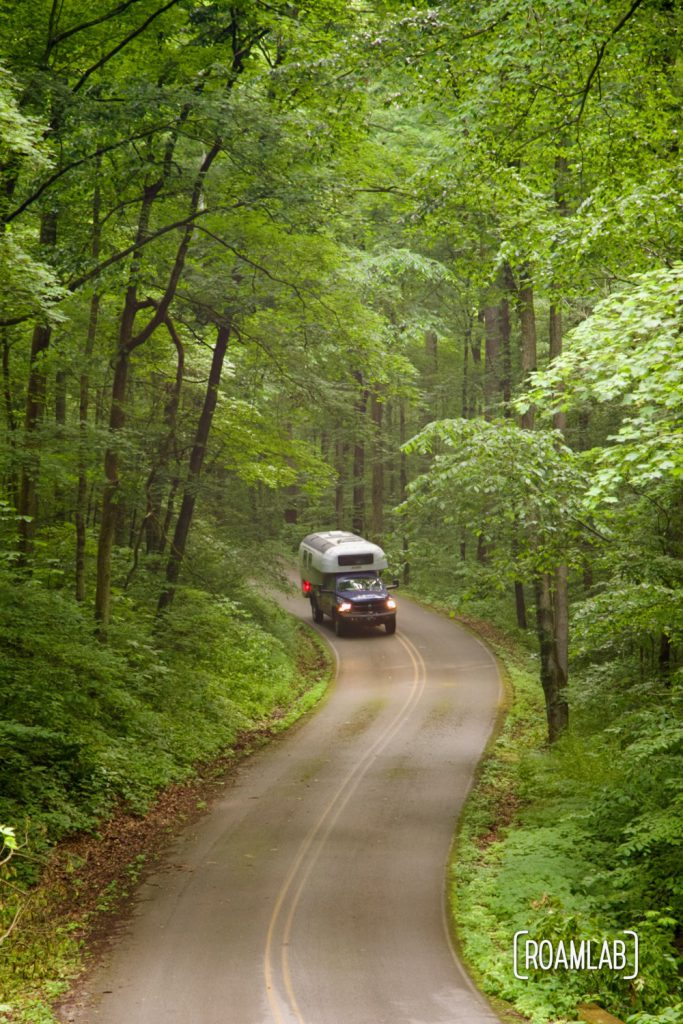 1970 Avion C11 truck camper driving down the winding paved two-lane Houchin Ferry Road in Mammoth Cave National Park.