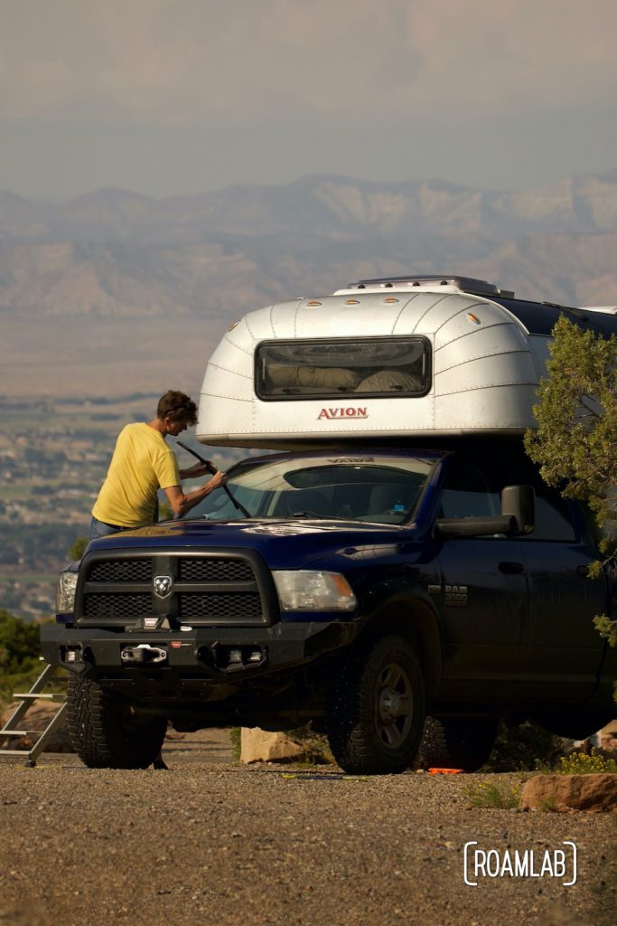 Man sitting on the hood of a blue truck with a 1970 Avion C11 truck camper at Saddlehorn Campground in Colorado National Monument.