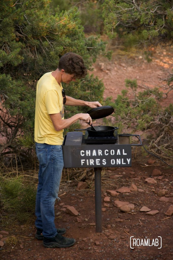 """Man looking into a cast iron skillet on top of a grill with """"Charcoal fires only"""" spray painted on the side."""