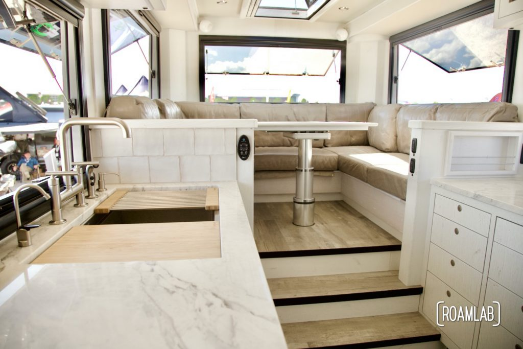 Earth Roamer interior featuring a marble counter top, stainless steal fixtures, and lots of windows.