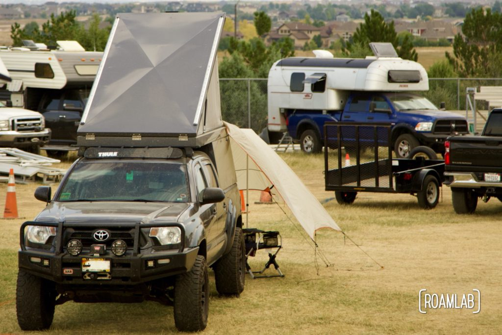 A collection of overland vehicles including truck campers and a popup roof tent camping at Overland Expo Mountain West in Loveland, Colorado.