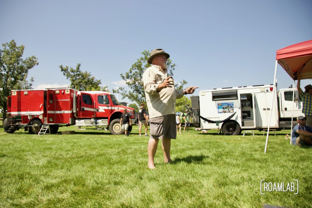 Man standing on a grassy lawn between custom overland vehicles.
