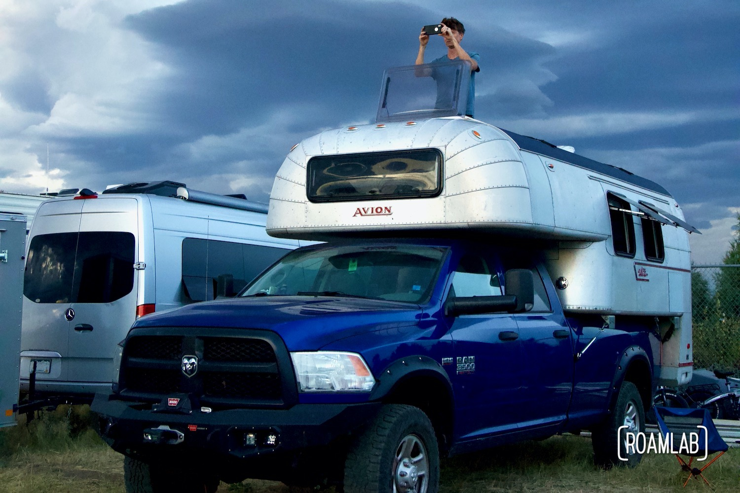 Man Looking out a room hatch at a 1970 Avion C11 truck camper as heavy storm clouds roll in.