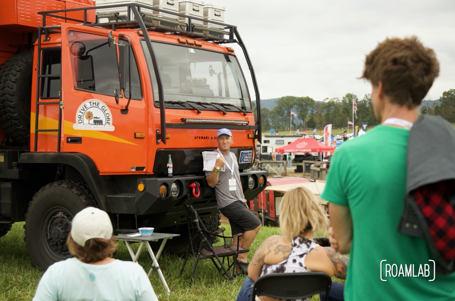 Man presenting massive orange rig to a group of seated onlookers at Overland Expo East 2021 in Arrington, Virginia.